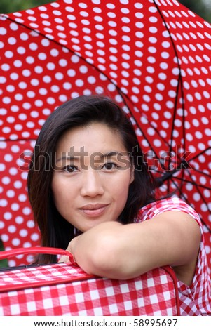 Attractive young Asian woman waiting with a suitcase and dotted umbrella - stock photo