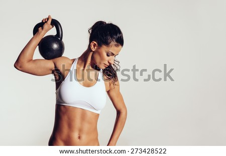 Attractive young athlete with muscular body exercising crossfit. Woman in sportswear doing crossfit workout with kettle bell on grey background. - stock photo