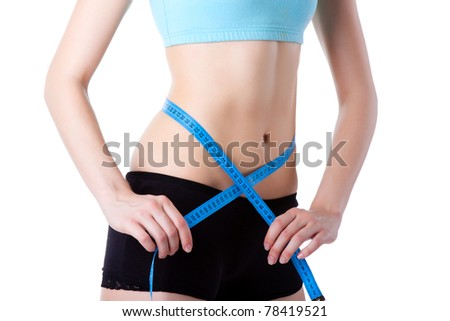 Attractive young athletic and sexy woman measuring size of her waist with a tape measure, wear blue top. Vertical shot. Isolated on white background. Fitness concept. - stock photo