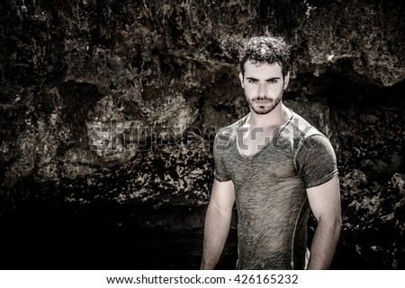 Attractive young athletic man in the sea or ocean by the rocky shore, wearing wet t-shirt, serious expression - stock photo