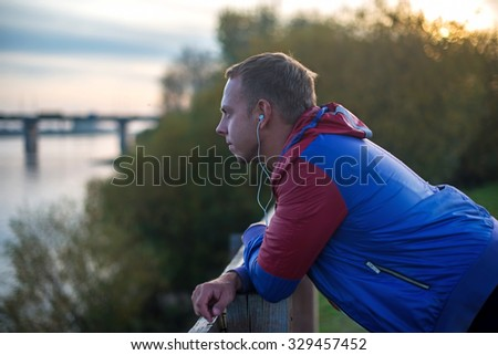 Attractive young athletic man standing on the beach and looks into the distance of the river to the bridge, listening to music. - stock photo