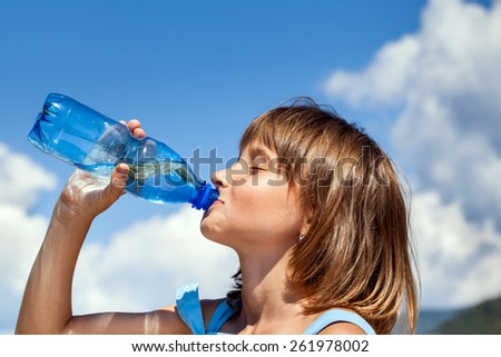 Attractive young beautiful girl drinking water from plastic bottles - stock photo