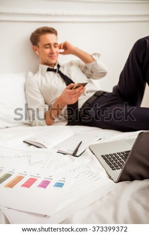 Attractive young blond businessman in white classical shirt and dark tie smiling, listening to music and resting while lying on bed - stock photo