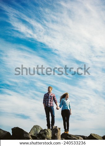 Attractive Young Blond Couple, standing on rocks, with bright blue sky behind