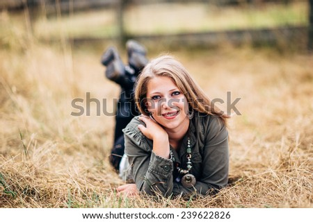 Attractive Young Blond Woman laying in straw feet up laughing, hand on shoulder - stock photo