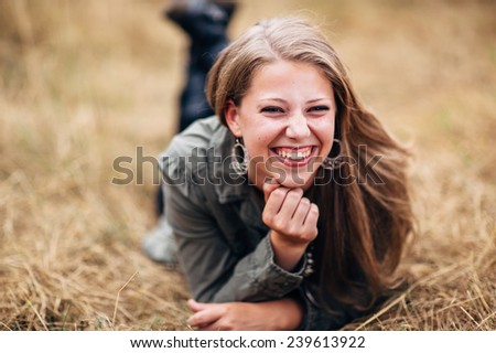 Attractive Young Blond Woman laying in straw laughing - stock photo