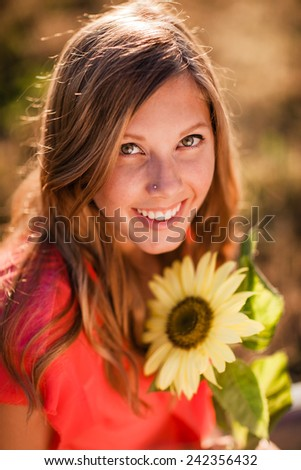 Attractive Young Blond Woman looking up at camera holding a sunflower - stock photo