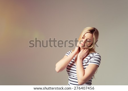 Attractive young blond woman relaxing and stretching her neck to the side with her eyes closed in pleasure on a grey background with copyspace - stock photo