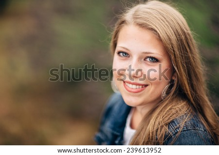 Attractive Young Blond Woman sitting on ground, smiling, jean jacket close up - stock photo
