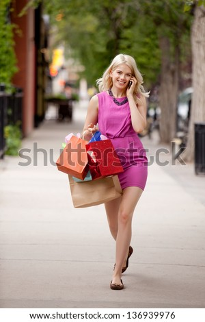 Attractive young blond woman walking down street talking on cell phone
