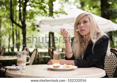 Attractive young blonde eating in a restaurant - stock photo