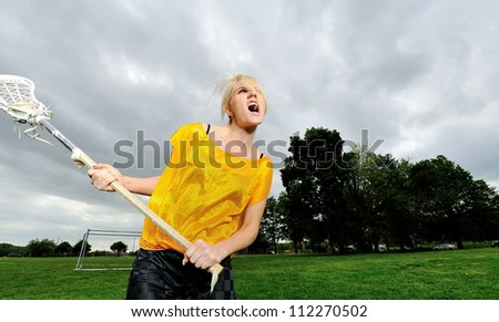 Attractive young blonde female lacrosse player screams as she shoots the ball - stock photo