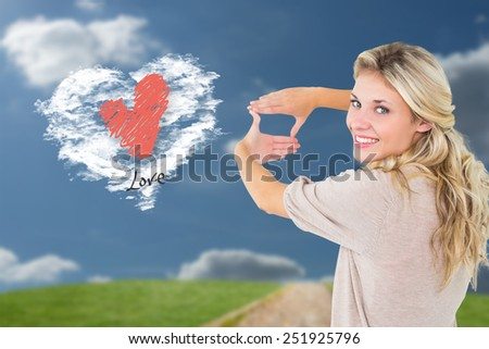 Attractive young blonde framing with her hands against cloud heart - stock photo