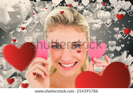 Attractive young blonde holding little hearts against grey valentines heart pattern - stock photo