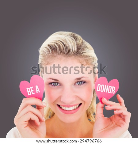 Attractive young blonde holding little hearts against grey vignette - stock photo