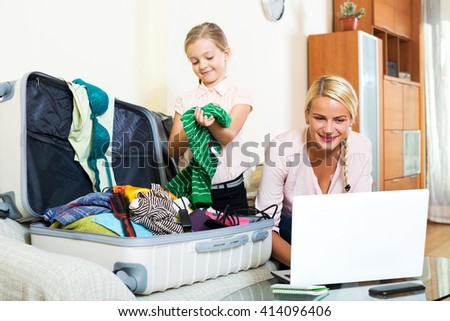 Attractive young blonde mother and little girl with luggage browsing web - stock photo