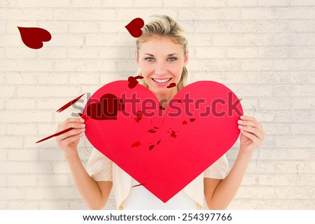 Attractive young blonde showing red heart against white wall - stock photo