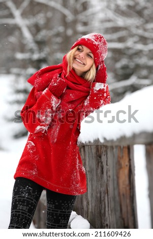 Attractive young blonde woman, leaning on the wooden bridge outside in wintertime. Girl wearing red clothing and surrounded by snow.