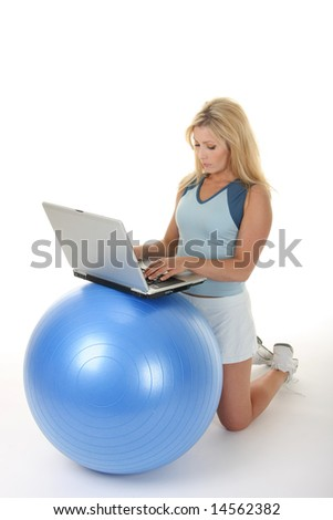 Attractive young blonde woman using an exercise ball as a desk for her laptop computer. - stock photo