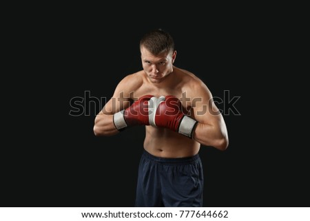 Attractive young boxer on black background