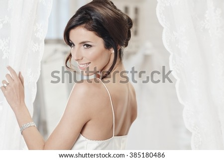 Attractive young bride in white slip, smiling. - stock photo