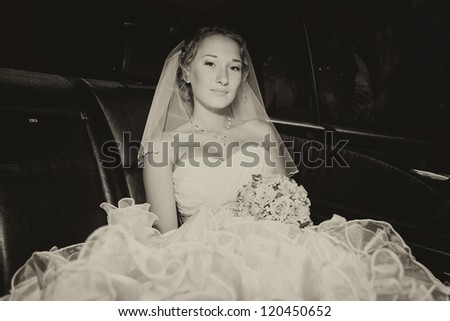 Attractive young bride posing with a bouquet in a luxurious car in her wedding day. series - stock photo