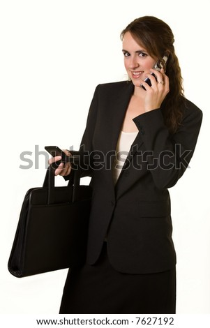 Attractive young brunette business woman talking on cell phone and text messaging at the same time wearing business suit and holding a briefcase to show busy