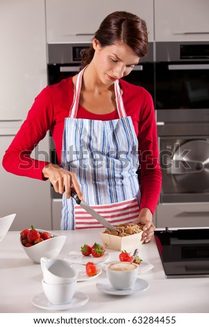 Attractive young brunette cutting the cake she just baked - stock photo