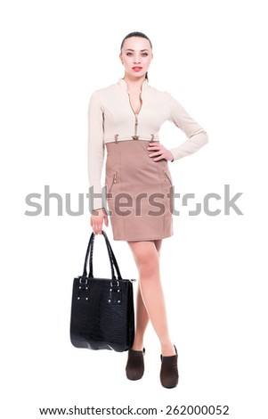 Attractive young brunette dressed in elegant dress with a bag. Isolated on white - stock photo