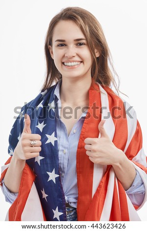 Attractive young brunette girl covered by National Flag celebrating Independence Day on 4th of July in United States of America.Cute model showing thumbs up on isolated white background - stock photo