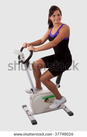 Attractive young brunette girl wearing fitness attire riding on a stationary exercise bike - stock photo
