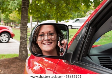 Attractive young brunette holding vehicle keys in rear view mirror. - stock photo