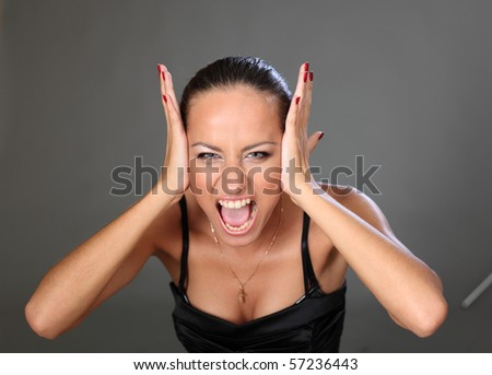 Attractive young brunette is crying in rage. - stock photo