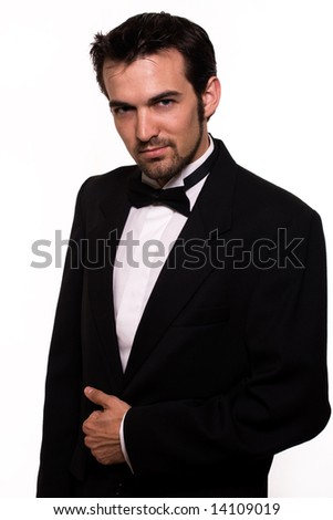 Attractive young brunette man with a beard wearing a black tuxedo - stock photo
