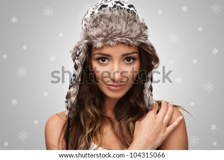 Attractive young brunette smiling with snowflakes in the background - stock photo