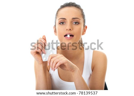 attractive young brunette takes some pills, isolated on white background - stock photo