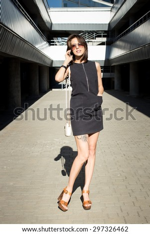 Attractive young brunette woman calling her model agency, holding mobile phone in her hand and standing outdoors in the city parking area on a bright sunny day - stock photo