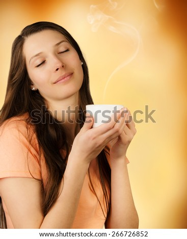 Attractive young brunette woman holding cup of coffee and enjoying smell of drink - stock photo