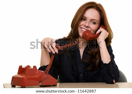 Attractive young brunette woman in business suit talking on an old style red phone smiling while sitting at a desk over white as if making personal phone calls while at work - stock photo