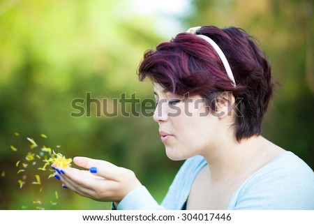 Attractive young brunette woman under soft natural lighting blowing flower petals from her hands. Shallow depth of field. - stock photo