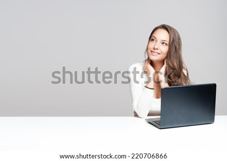Attractive young brunette woman using her laptop. - stock photo