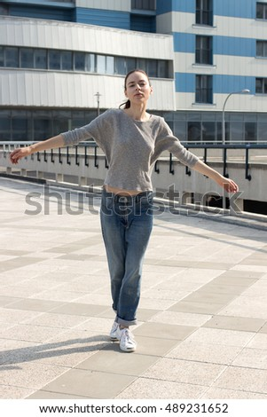 Attractive young brunette woman wearing casual street wear, moving near building