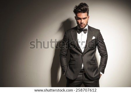 Attractive young business man looking at the camera while holding both hands in his pockets. - stock photo