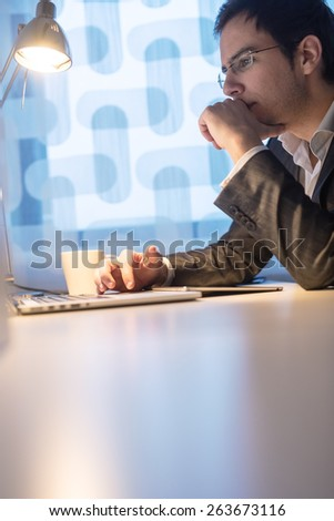 Attractive young business man working late hours at his office desk navigating the internet on his laptop computer while reading the screen, profile view. - stock photo