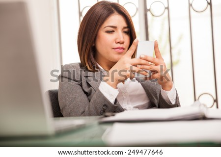 Attractive young business woman reading emails and working on her cell phone - stock photo