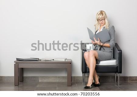Attractive young business woman sitting in a chair. Waiting room. - stock photo