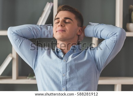 Attractive young businessman is keeping hands behind head while resting in office