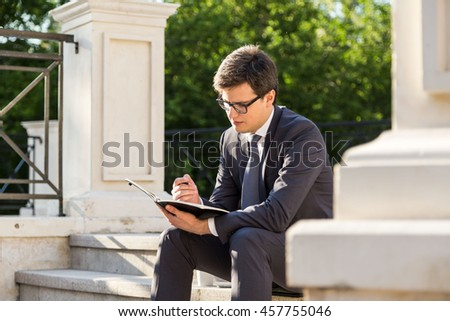 Attractive young businessman making notes in notepad while sitting on stairs outside. Concrete columns and trees in the background