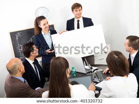 Attractive young businessman presents new development plan at poster - stock photo