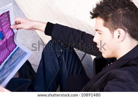 Attractive young businessman reading colored newspaper - stock photo